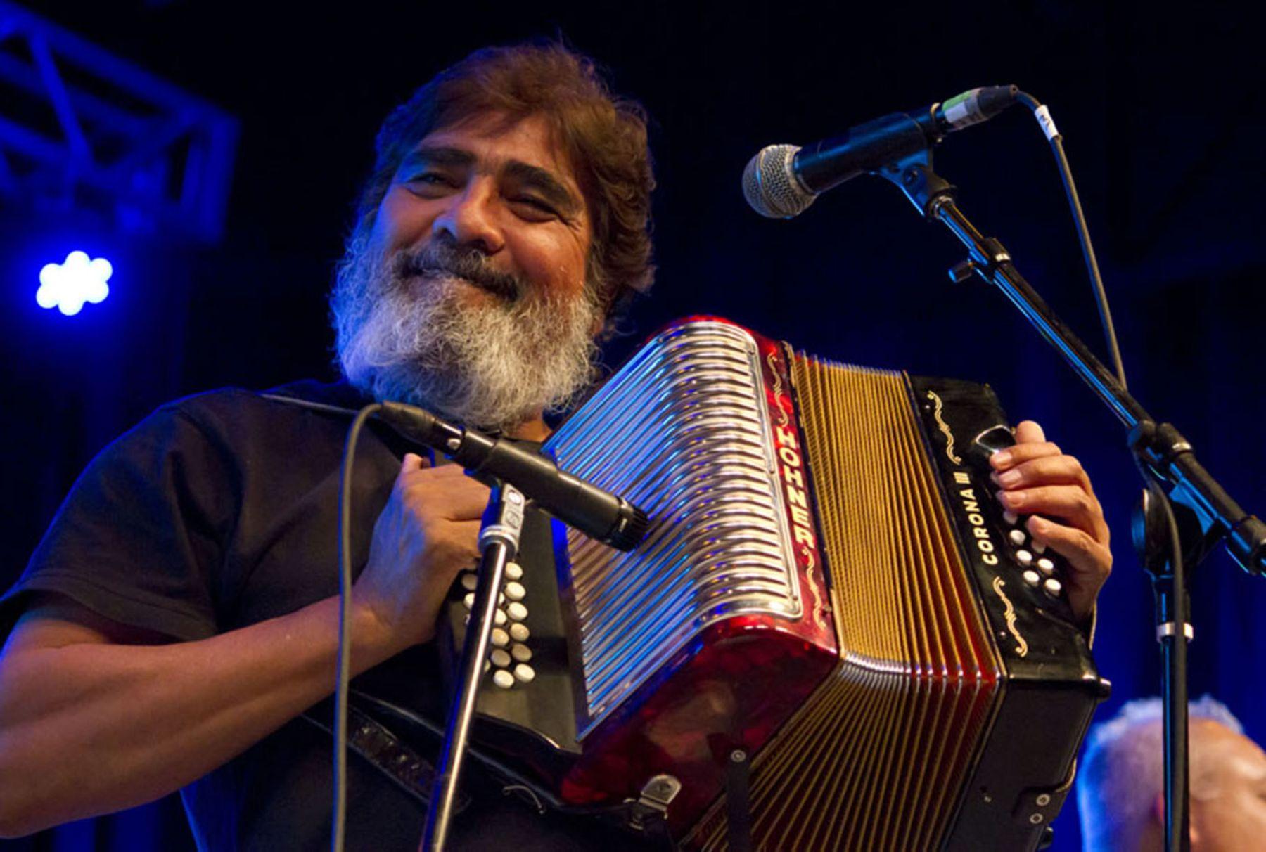 Celso Piña tocando el acordeón en un concierto