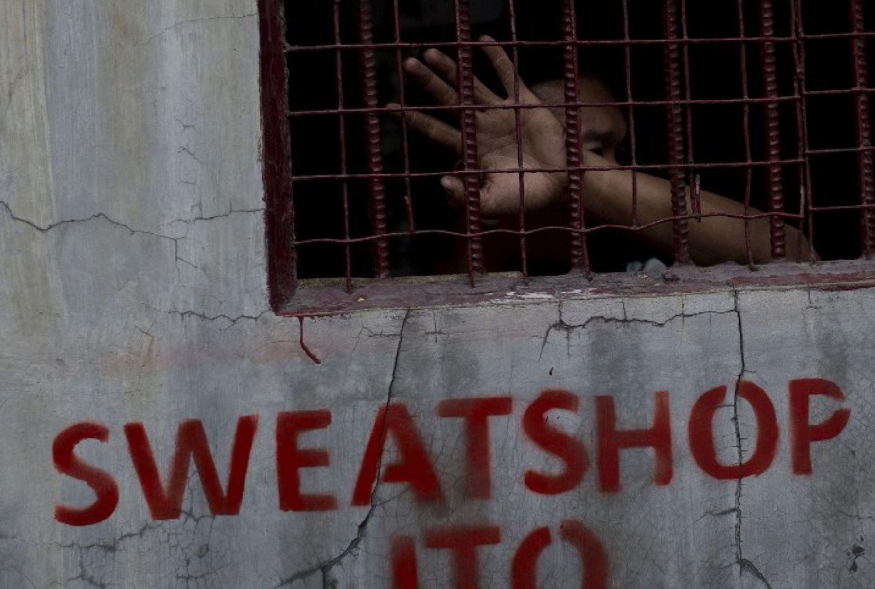 Un trabajador de la fábrica de calzado se asoma desde la ventana frente a las puertas de una fábrica de calzado, nueve días después que la fábrica fuera destruida por un incendio matando a 72 de sus trabajadores.Foto:AFP