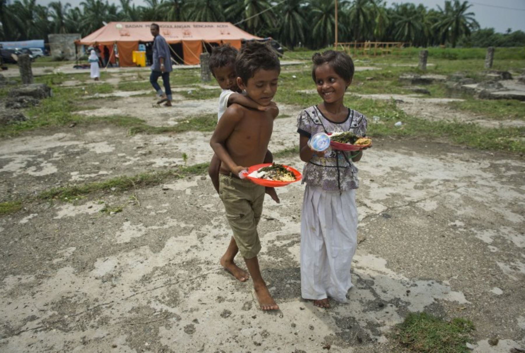 Niños de Myanmar llevan su comida en el campamento creado en Bayeun, después de más de 400 inmigrantes rohingya de Myanmar y Bangladesh fueron rescatados por pescadores indonesios. Foto:AFP