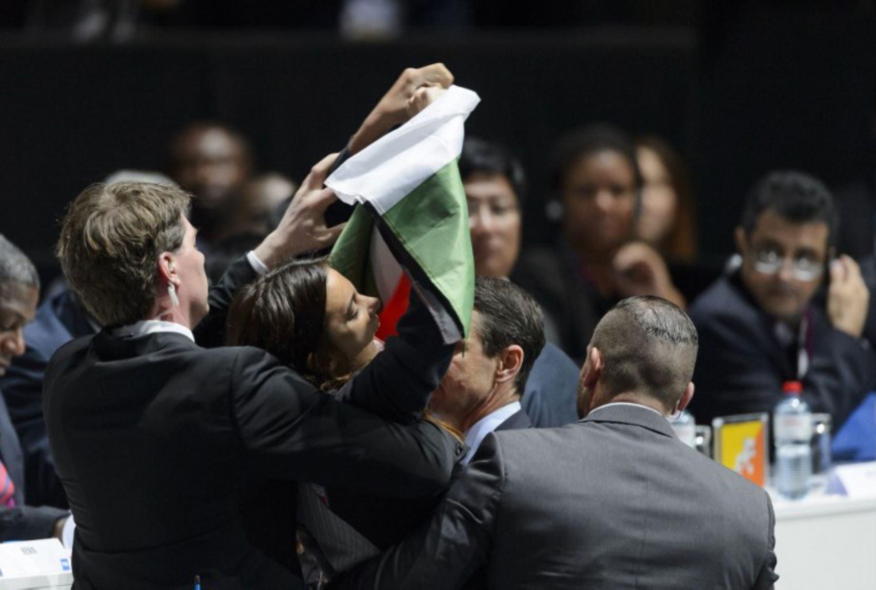 Agentes de seguridad evacuan un manifestante que sostiene una bandera palestina quien pide expulsar a Israel de la FIFA . Foto:AFP
