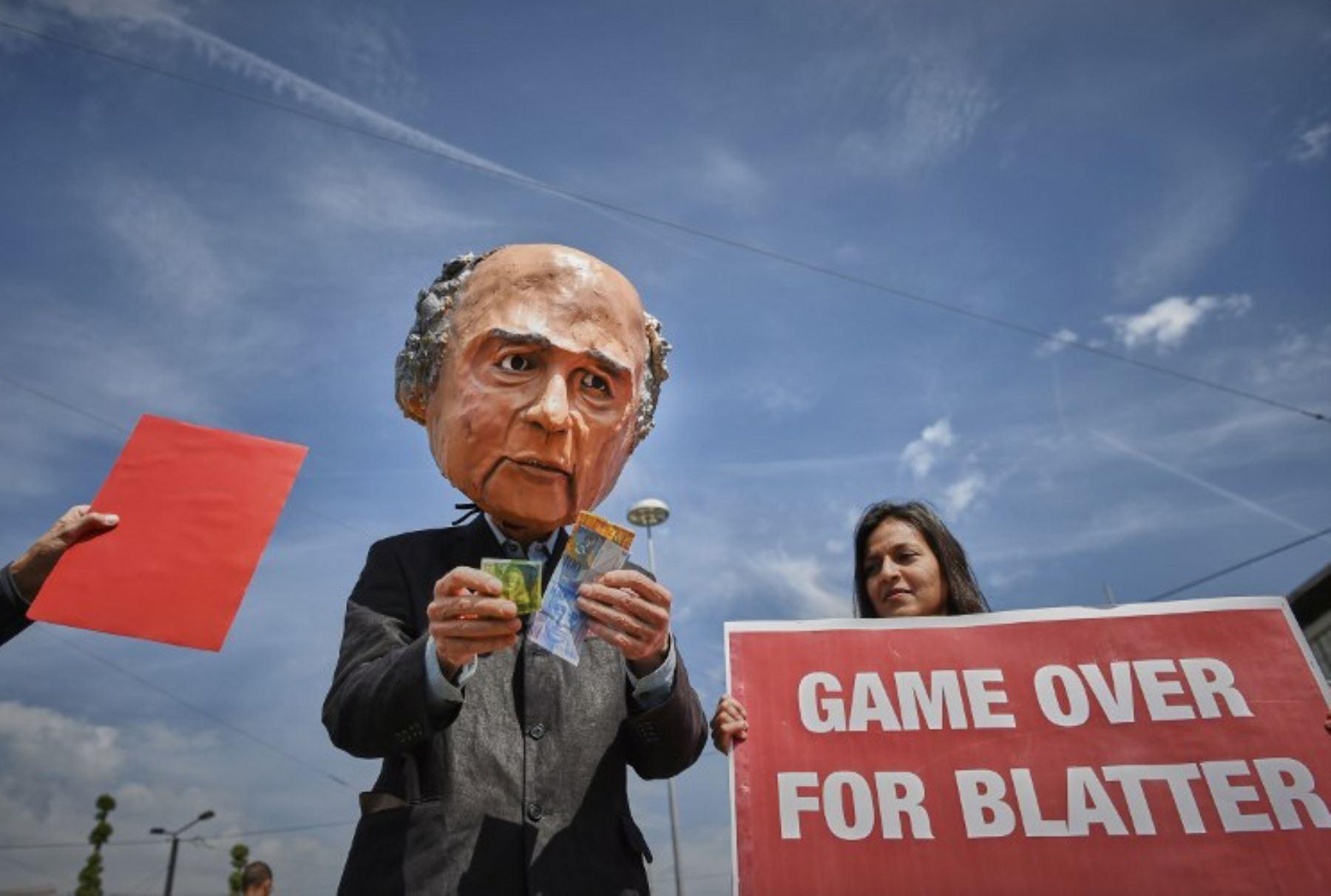 Un hombre con una mascara del presidente de la FIFA, Joseph Blatter, sostiene una pancarta durante una protesta celebrada frente al Hallenstadium. Foto:AFP