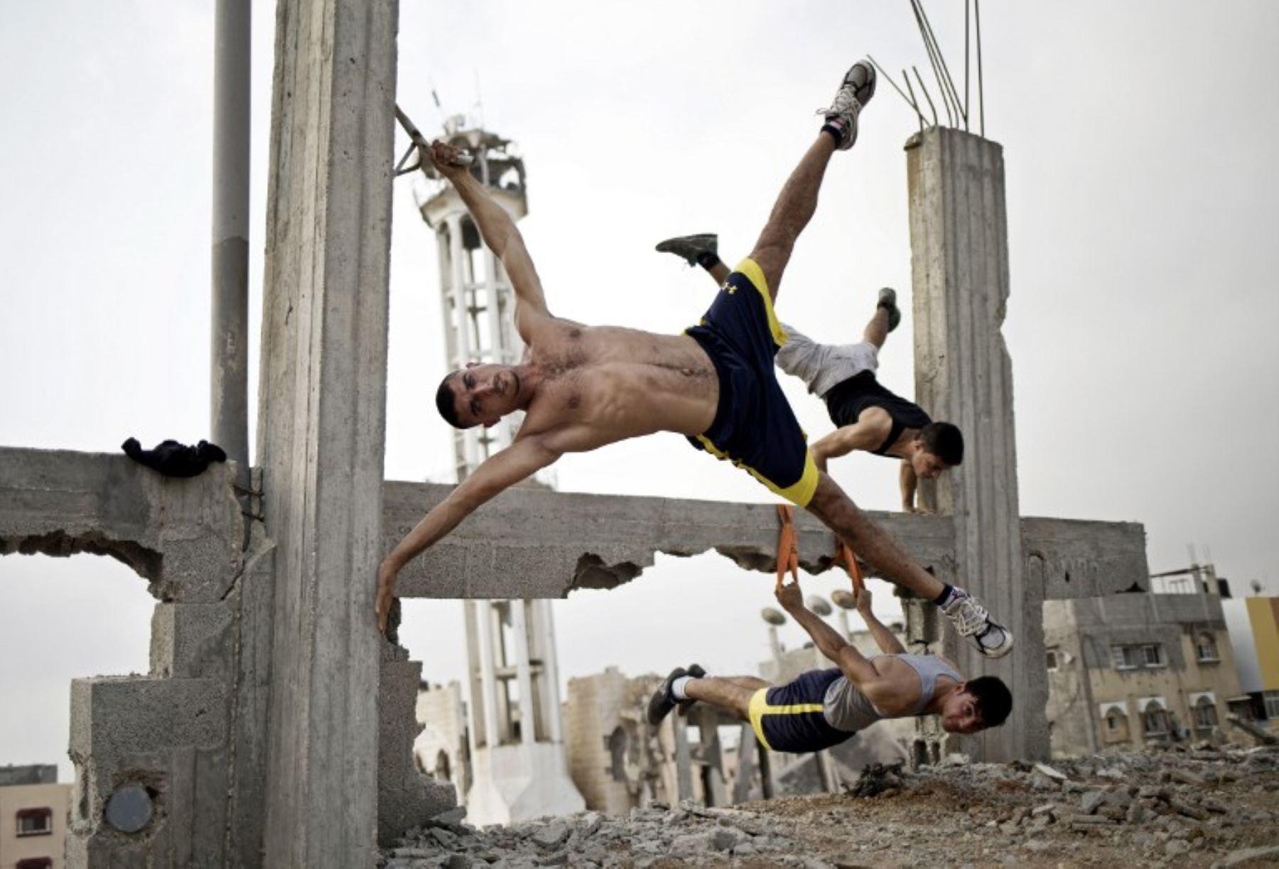 Palestinos realizan ejercicios en medio de la destrucción de la ciudad de Gaza. Foto: AFP