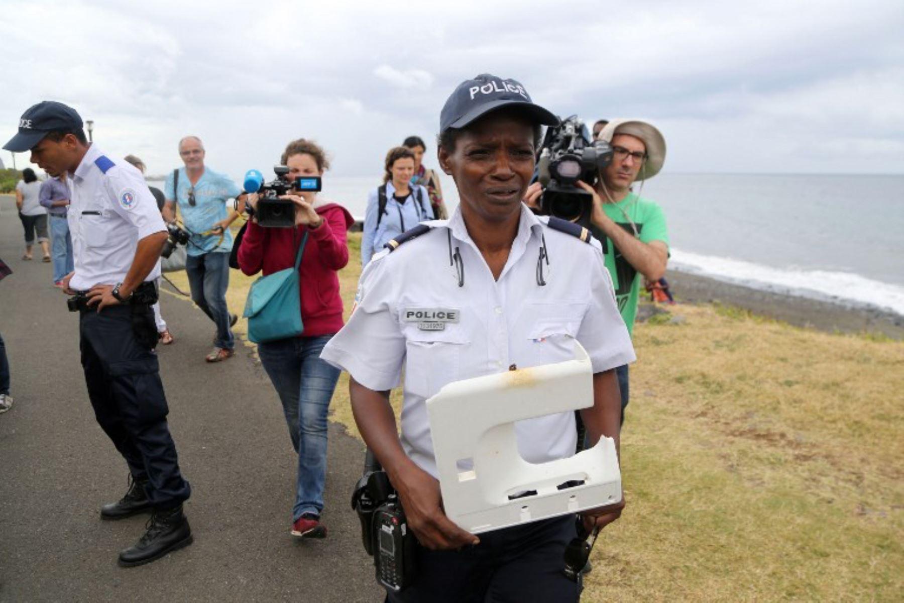 Un oficial de policía tiene un pedazo de plástico del resto de un avión varado en la isla francesa del Océano Índico. Foto: AFP