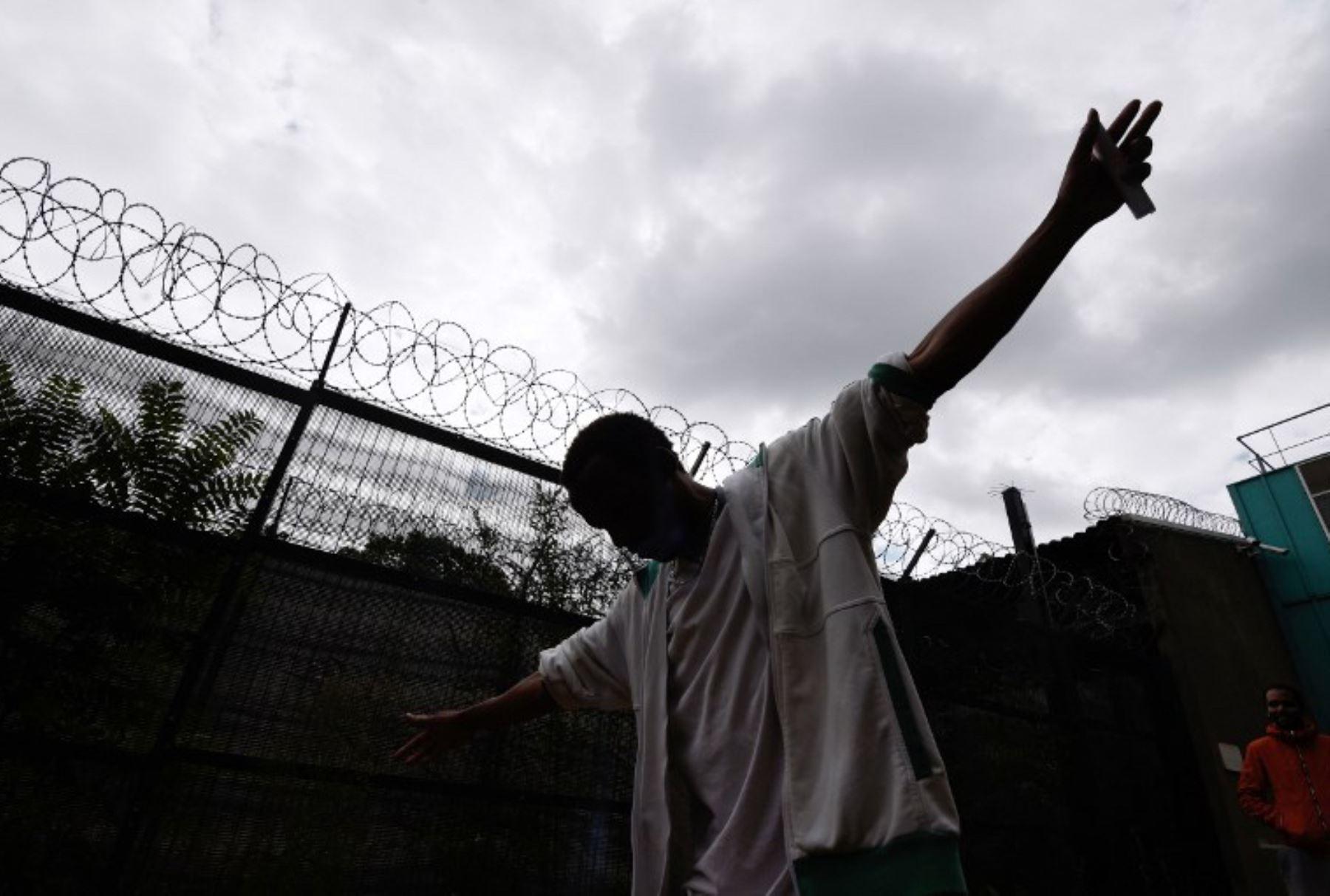 Un hombre levanta los brazos cerca de una cerca de alambre de púas en un centro para los migrantes alojados en un antiguo lugar de detención en París. Foto: AFP