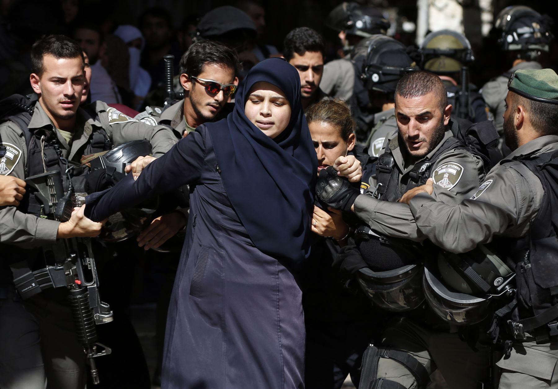 Las fuerzas de seguridad israelíes detienen a joven palestina durante enfrentamientos entre manifestantes palestinos y policías israelíes. Foto: AFP
