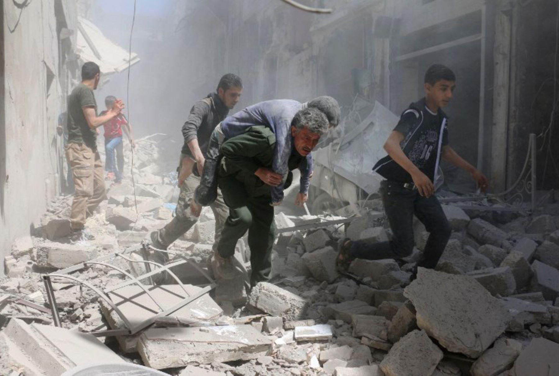 Sirios evacuan un herido en medio de los escombros de edificios destruidos tras un ataque aéreo. Foto: AFP