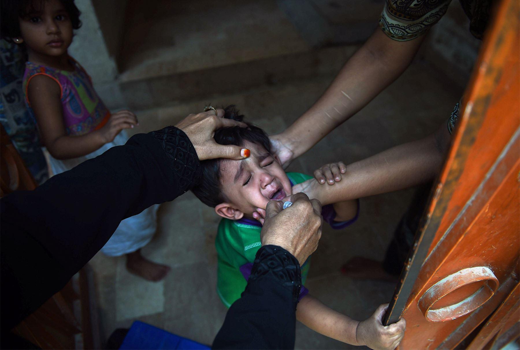 Un trabajador de la salud de Pakistán administra la vacuna contra la poliomielitis a un niño durante una campaña de vacunación puerta a puerta en Karachi el 24 de mayo de 2016.  FOTO AFP / ASIF HASSAN