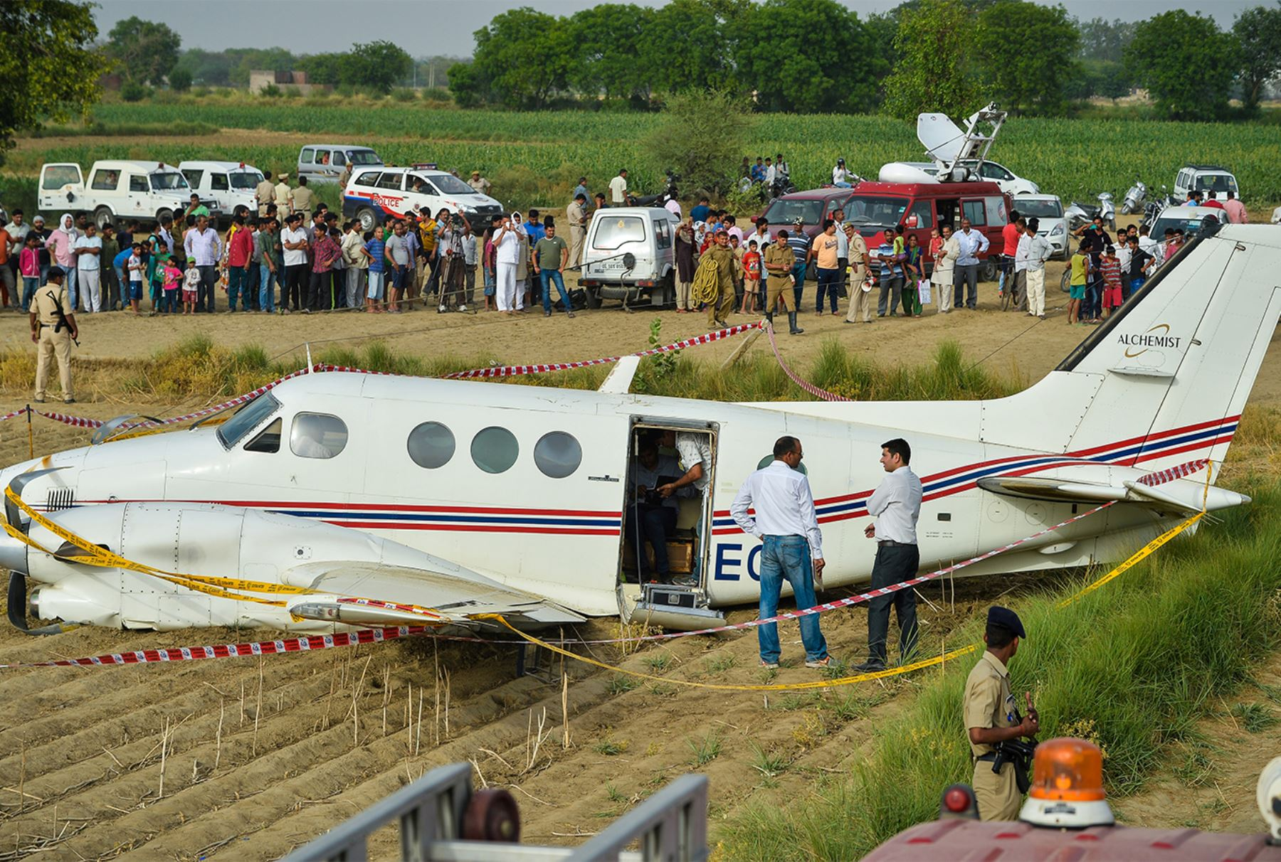 Personal de emergencia se y decenas de curiosos rodean los restos de un avión que se estrelló en un campo en las afueras de Nueva Delhi el 24 de mayo de 2016.  AFP PHOTO / CHANDAN KHANNA