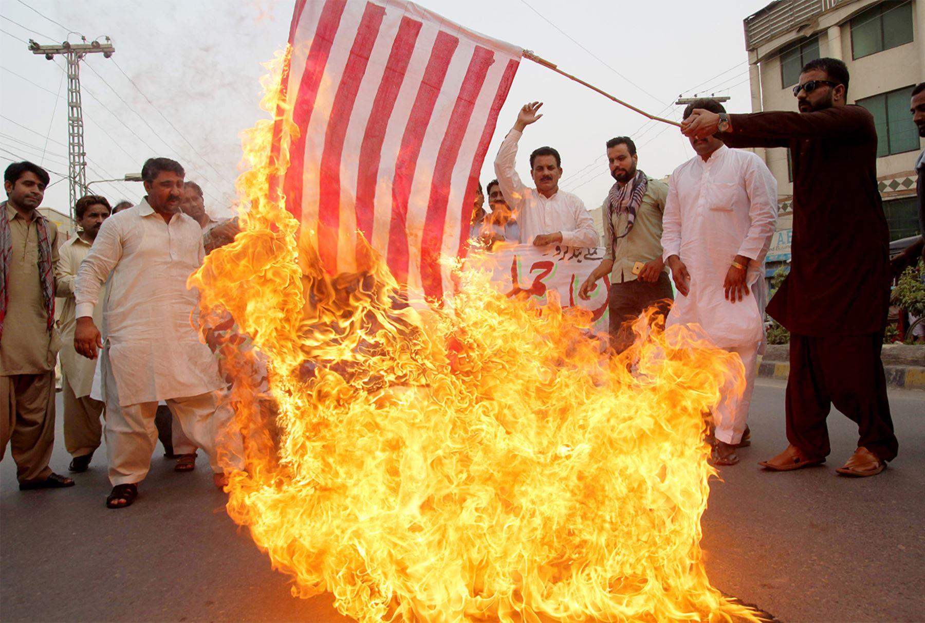 Un manifestante paquistaní sostiene una bandera de Estados Unidos ardiendo mientras los demás gritan consignas durante una protesta en Multan el 24 de mayo de 2016, contra un ataque de drone estadounidense en la provincia suroccidental paquistaní de Baluchistán.  AFP PHOTO / SS MIRZA