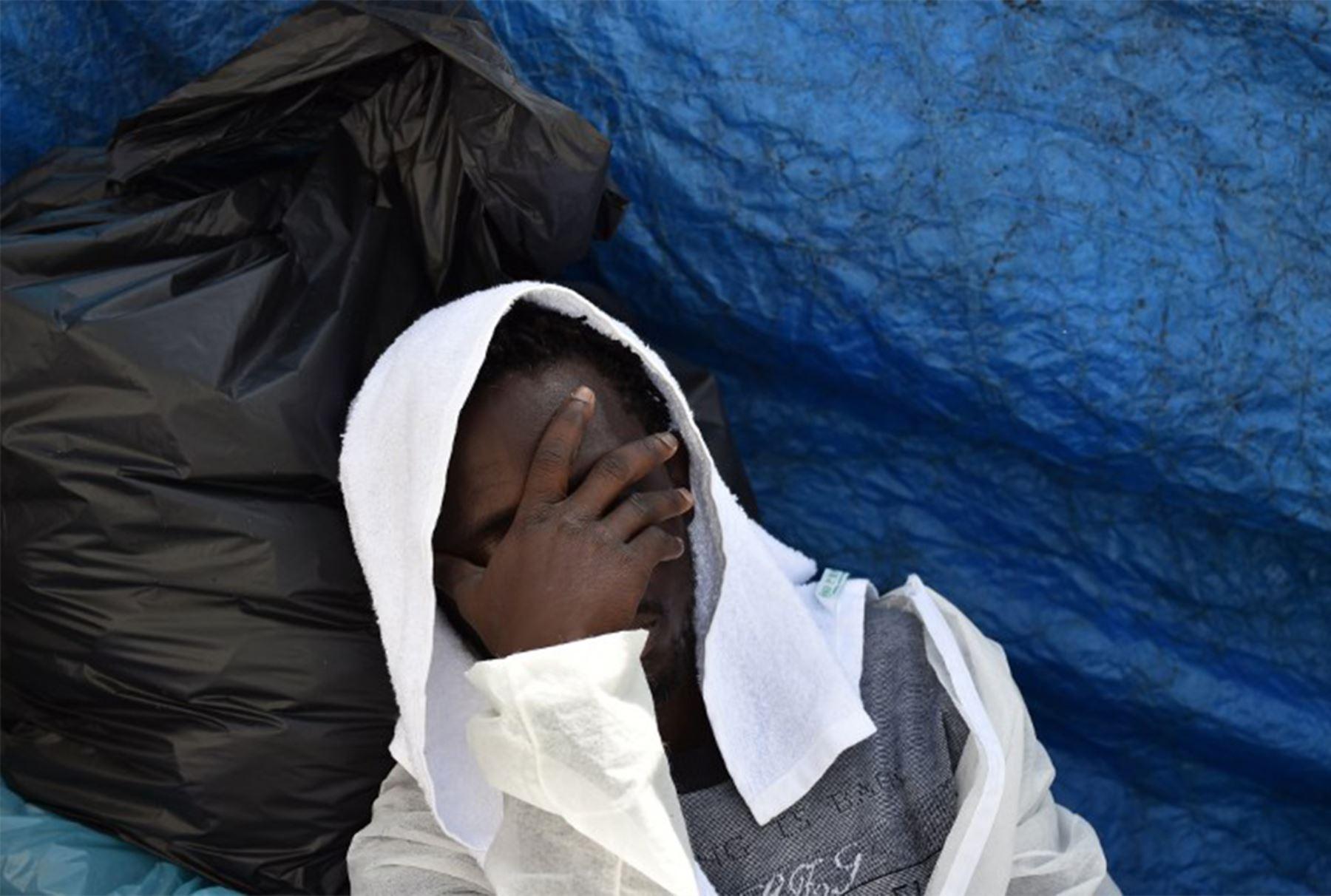 """Un hombre descansa mientras espera comida a bordo del barco de rescate """"Aquarius"""", el 25 de mayo, el año 2016 un día después de una operación de rescate de los migrantes y refugiados de la costa libia.   FOTO AFP / GABRIEL BOUYS"""