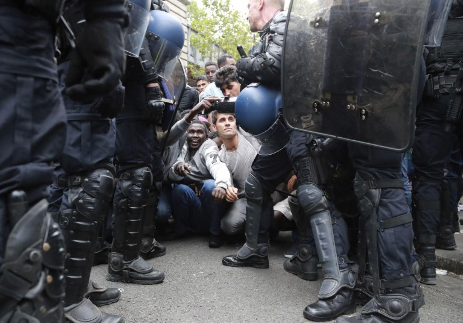 Migrantes son expulsados de un campamento improvisado por policías franceses. Foto: AFP