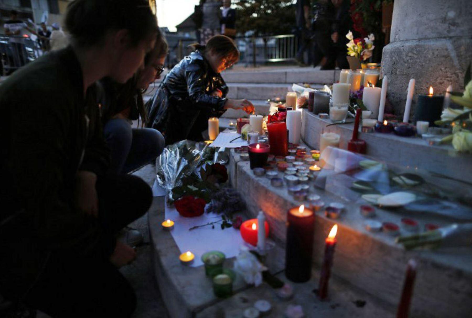 Una mujer coloca una vela y flores en homenaje al sacerdote asesinado en una iglesia en Francia. Foto: AFP