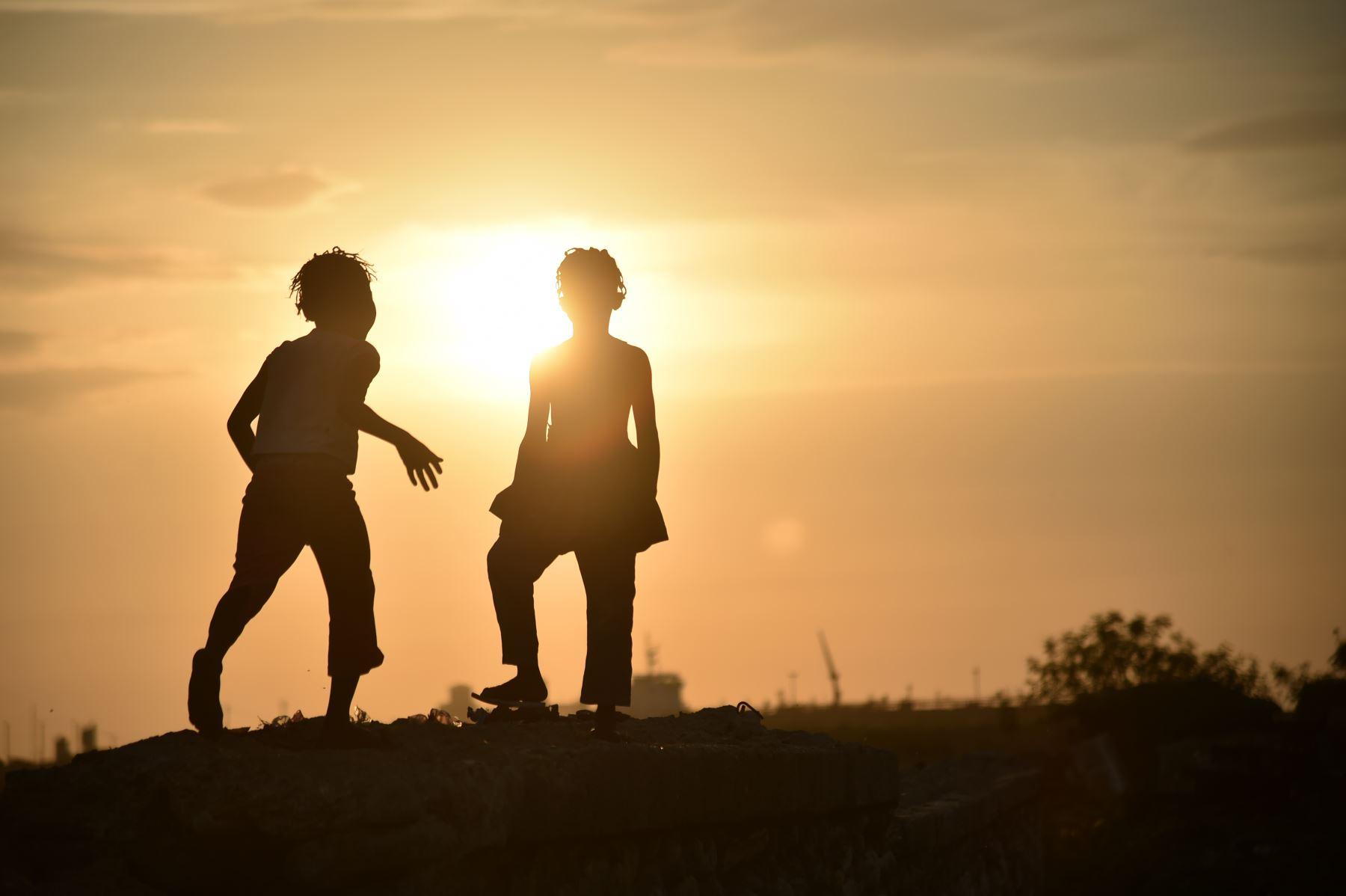 Dos niñas juegan en una pequeña pared durante la puesta del sol en un barrio de la comuna de Cité Soleil, Puerto Príncipe,  Foto: AFP