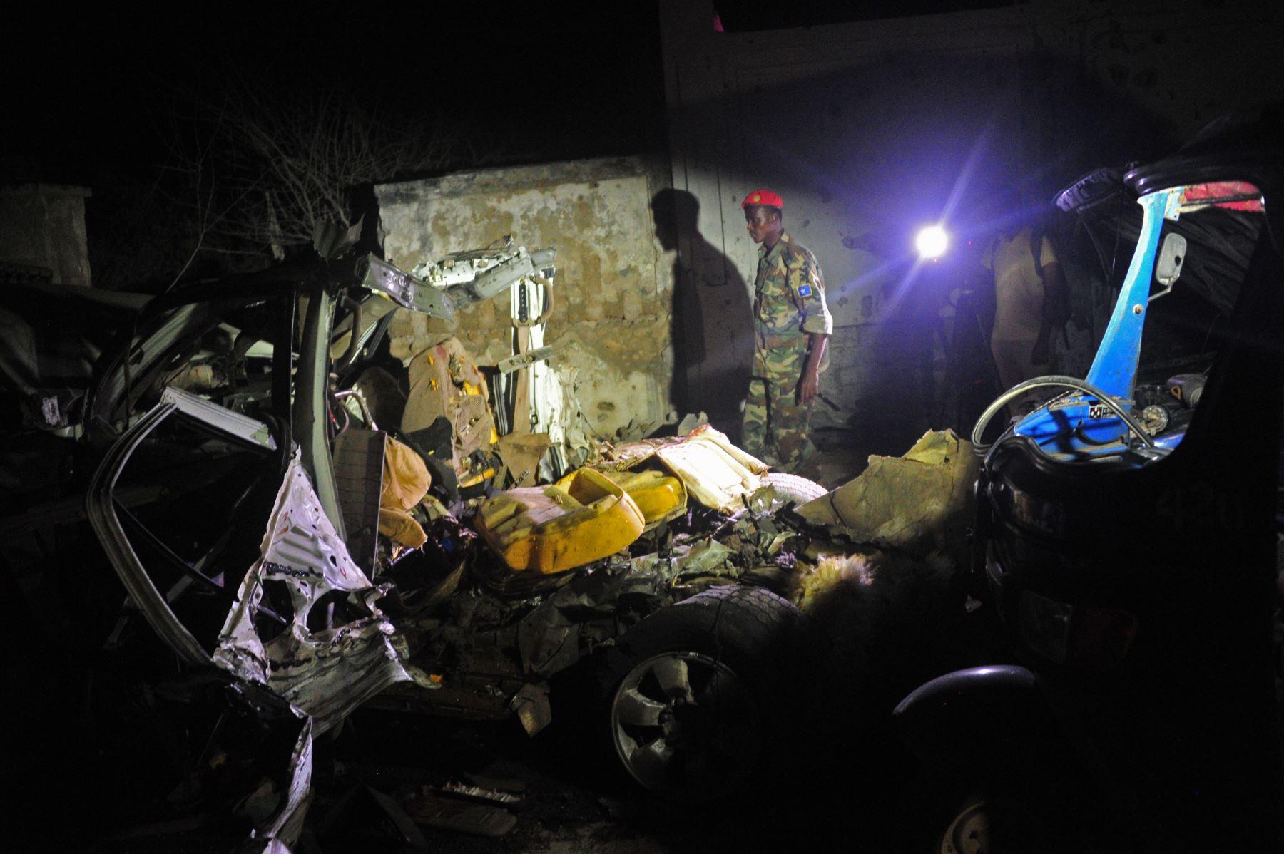 Un soldado somalí se encuentra junto a los restos del coche bomba fuera de un restaurante de la playa en la capital somalí, Mogadiscio, tras un ataque de presuntos rebeldes Shabaab, vinculada a Al Qaeda. Foto: AFP