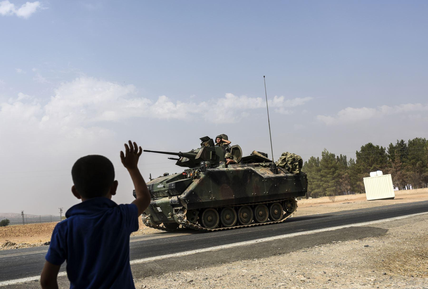 Un muchacho saluda  a convoy tanque turco que conduce en Siria desde la ciudad fronteriza turca de Siria Karkamış en la región sur de Gaziantep Foto: AFP