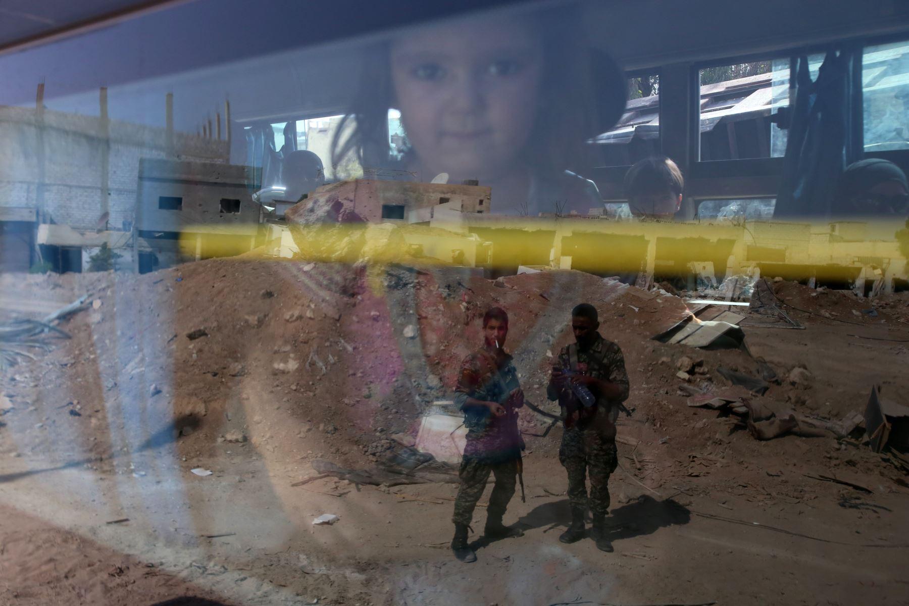 las tropas del gobierno sirio se ven reflejados en la ventana de un autobús que transportaba a las personas como parte de una evacuación de la ciudad de Daraya fuera de la capital Damasco  en virtud de un acuerdo alcanzado entre los combatientes del gobierno y de la oposición después de un ejército de cuatro años cerco. Foto: AFP