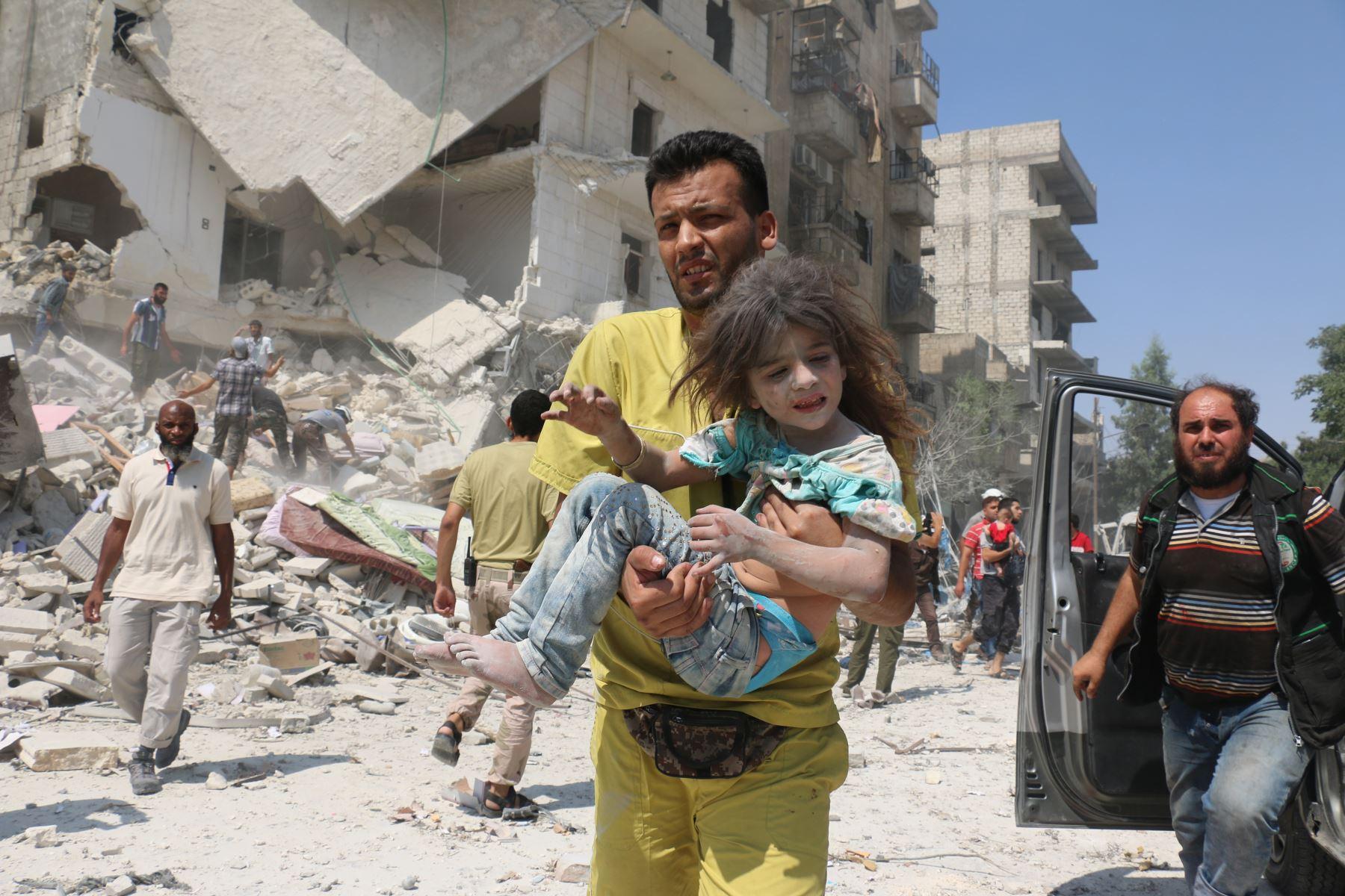 Un hombre sirio lleva un niño en el distrito de Maadi de Alepo, después que  los aviones del régimen lanzaron bombas de cañón repletos de explosivos Foto: AFP