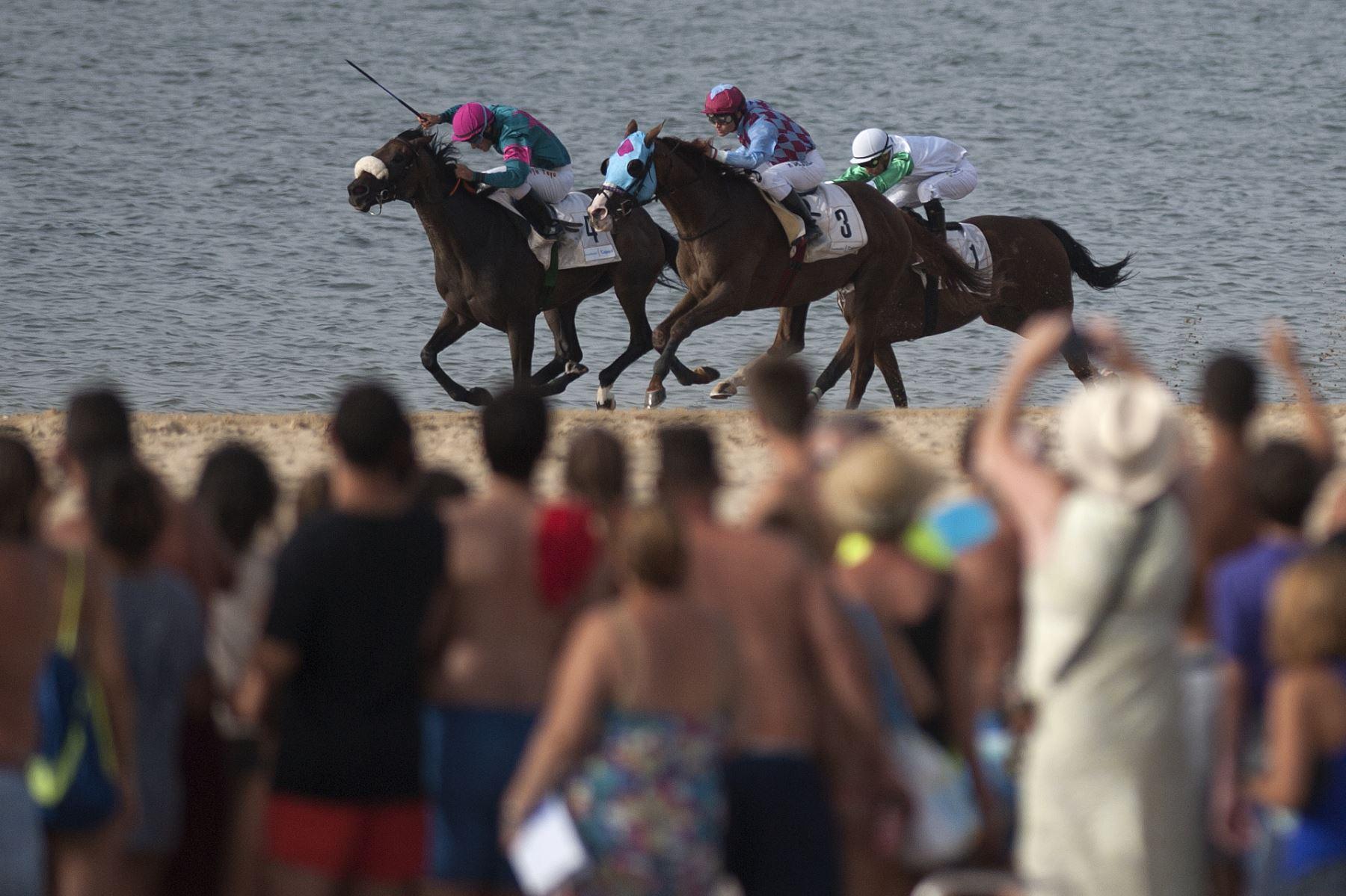 carrera de jinetes a lo largo de la playa durante la carrera anual de caballos en la playa de Sanlúcar de Barrameda, cerca de Cádiz Foto: AFP