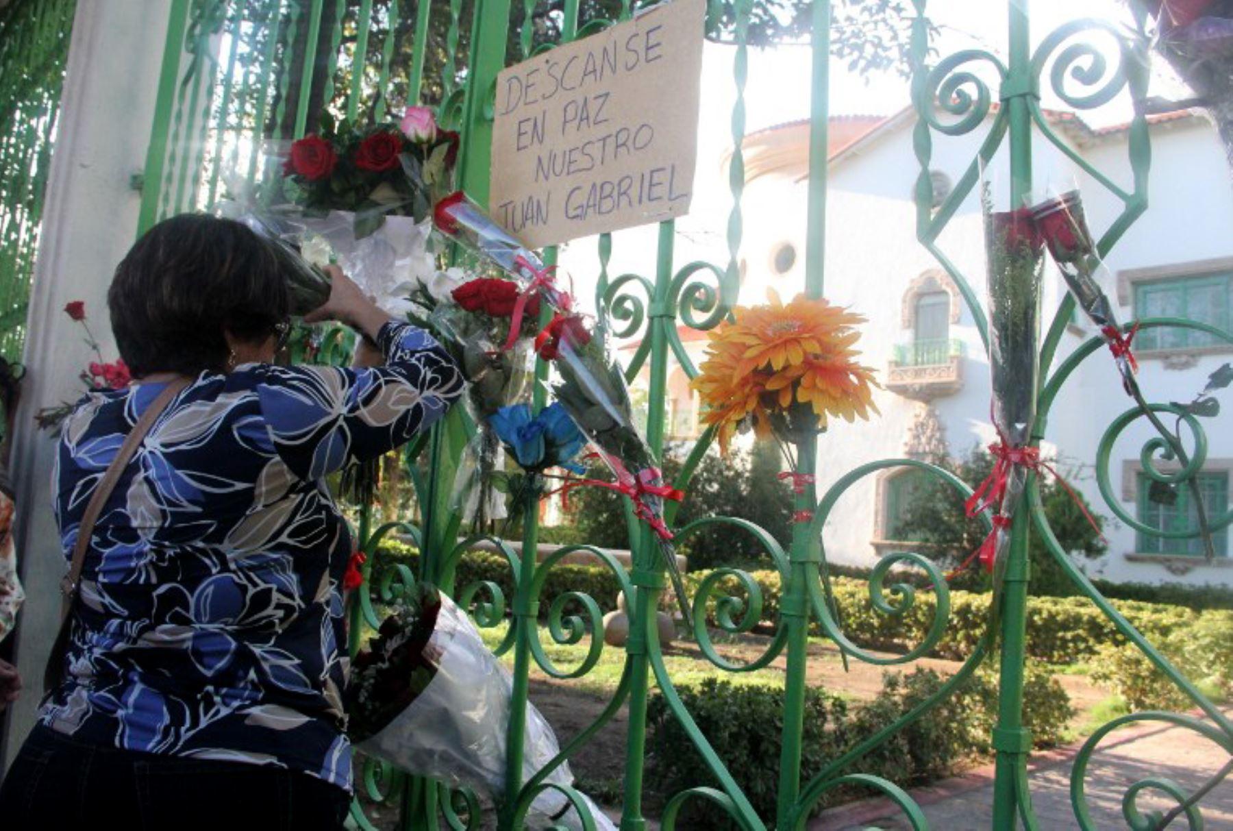 La gente pone flores en frente de la casa del cantante mexicano Juan Gabriel , en Ciudad Juárez. Foto: AFP