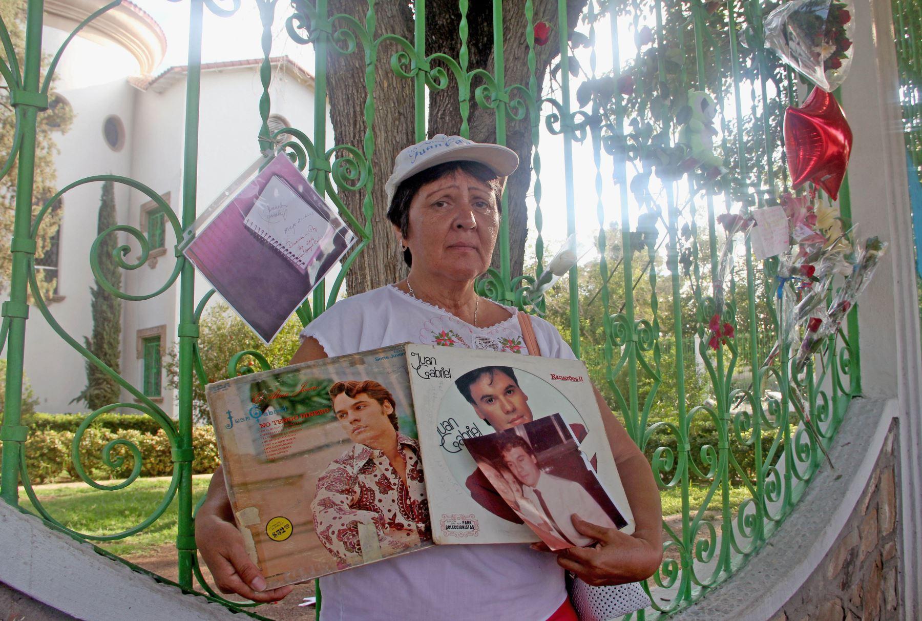 Una mujer posa con sus álbumes del cantante mexicano Juan Gabriel en el frente de su casa, en Ciudad Juárez, México. Foto: AFP