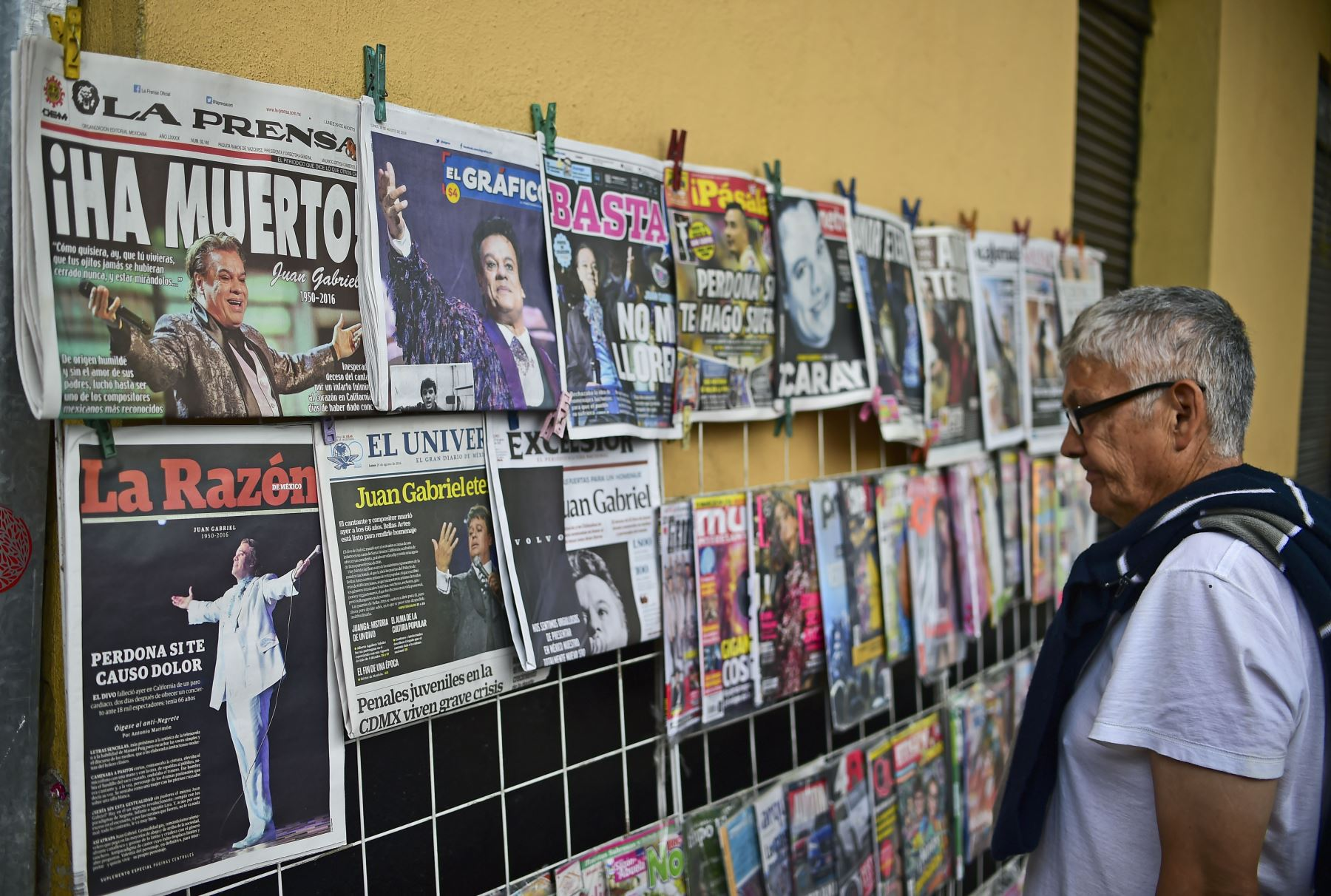Un hombre mira las portadas de los periódicos con la noticia de la muerte del cantante Juan Gabriel en la Plaza Garibaldi en Ciudad de México. Foto: AFP