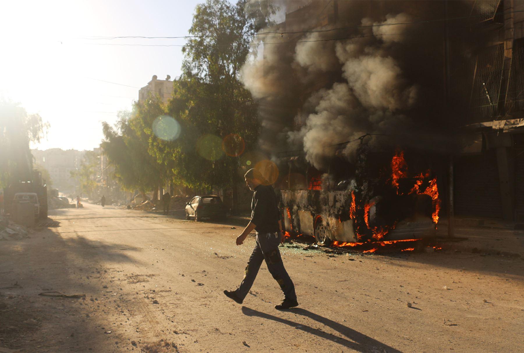 Un hombre sirio pasa junto a un autobús incendiado tras un ataque aéreo reportado en el distrito controlado por los rebeldes Salaheddin de Alepo.  Foto: AFP