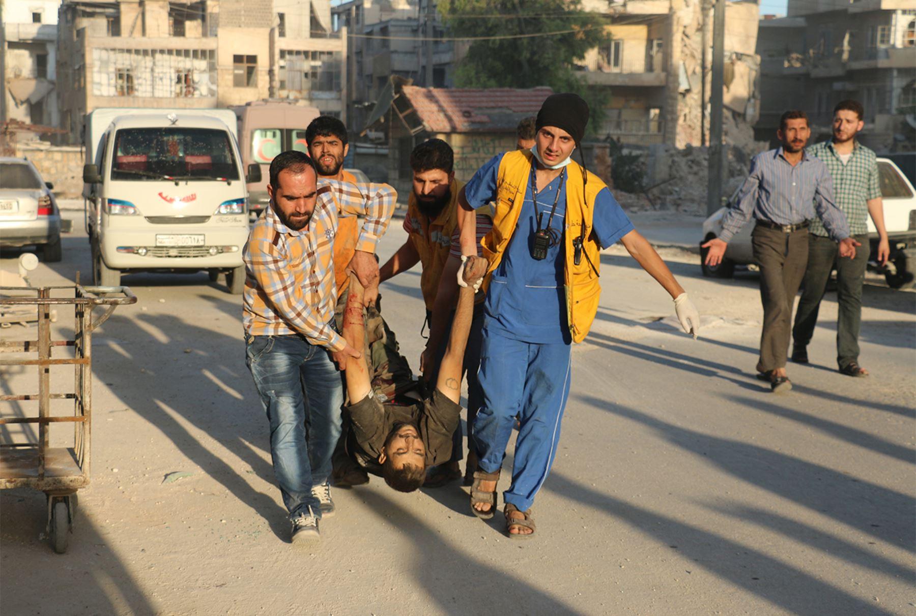 Trabajadores de rescate y residentes llevan el cuerpo de una víctima tras un ataque aéreo reportado en el distrito controlado por los rebeldes Salaheddin de Alepo el 25 de septiembre de 2016.  Foto:AFP
