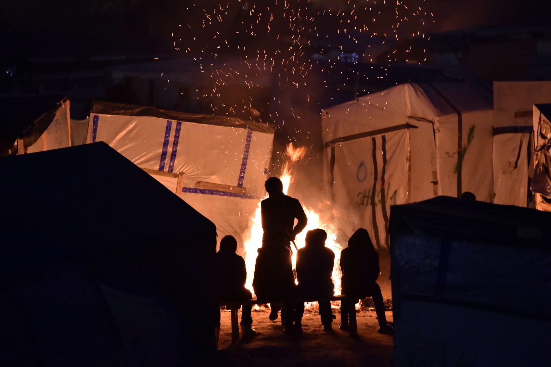 Migrantes se reúnen alrededor de una fogata en Calais, al norte de Francia. Foto: AFP