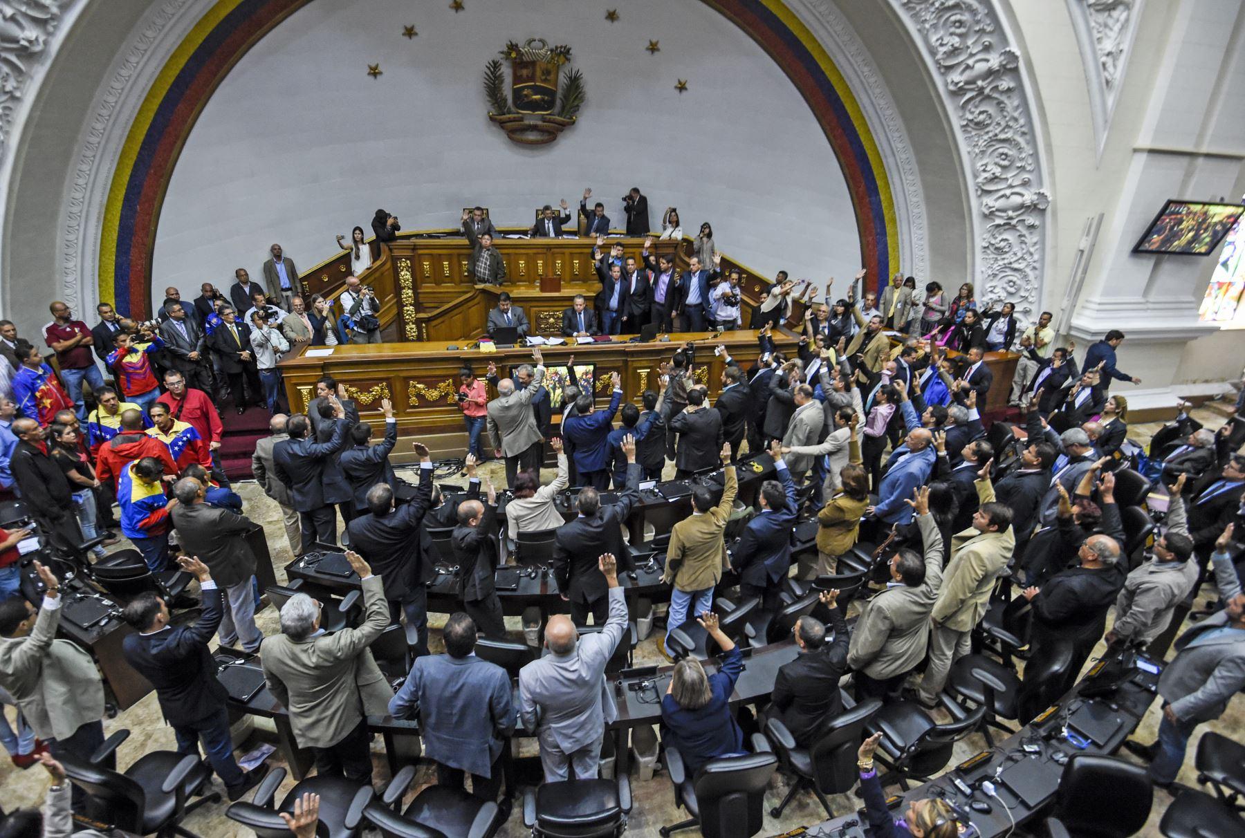 Diputados de la oposición levantan la mano durante la votación para abrir un juicio político contra el presidente Nicolás Maduro. Foto: AFP
