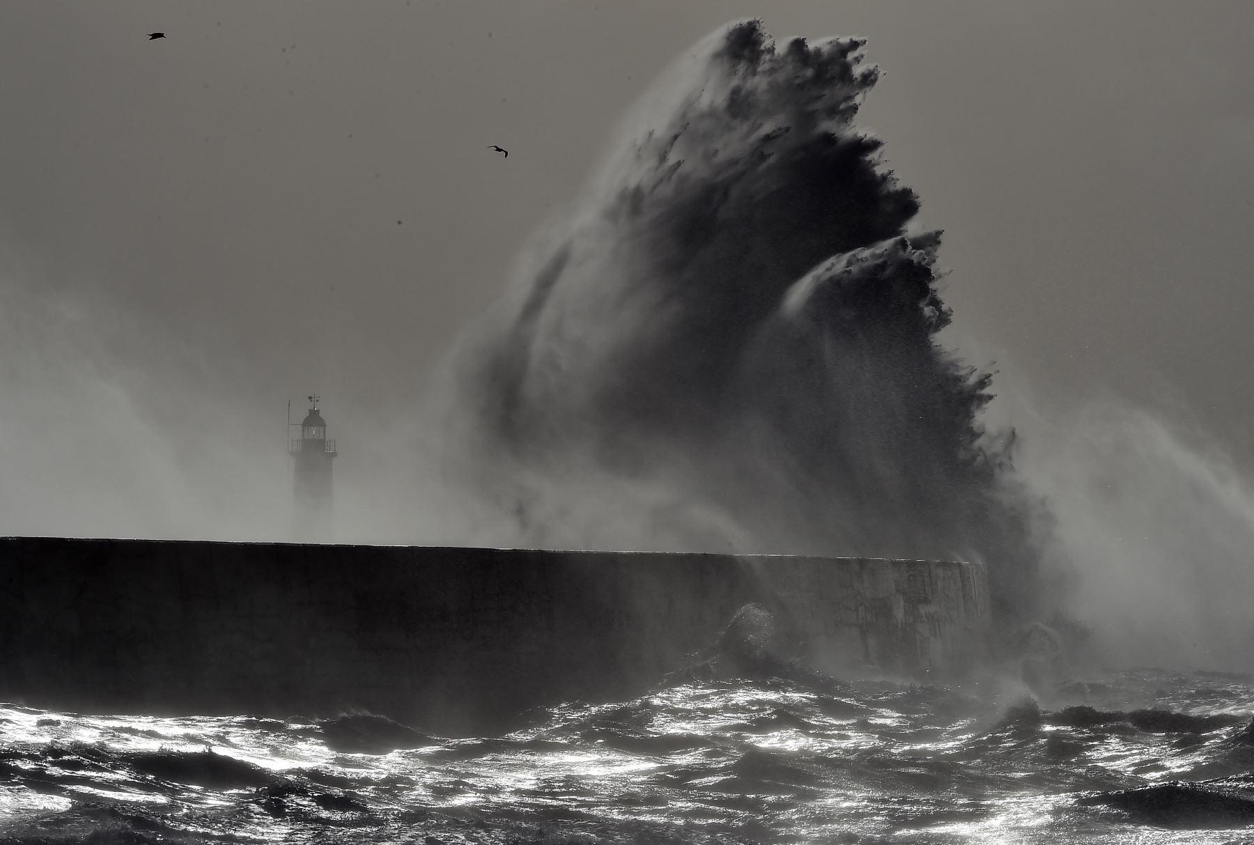 Olas golpean el muelle sobre el faro de Newhaven en la costa sur de Inglaterra. Foto: AFP