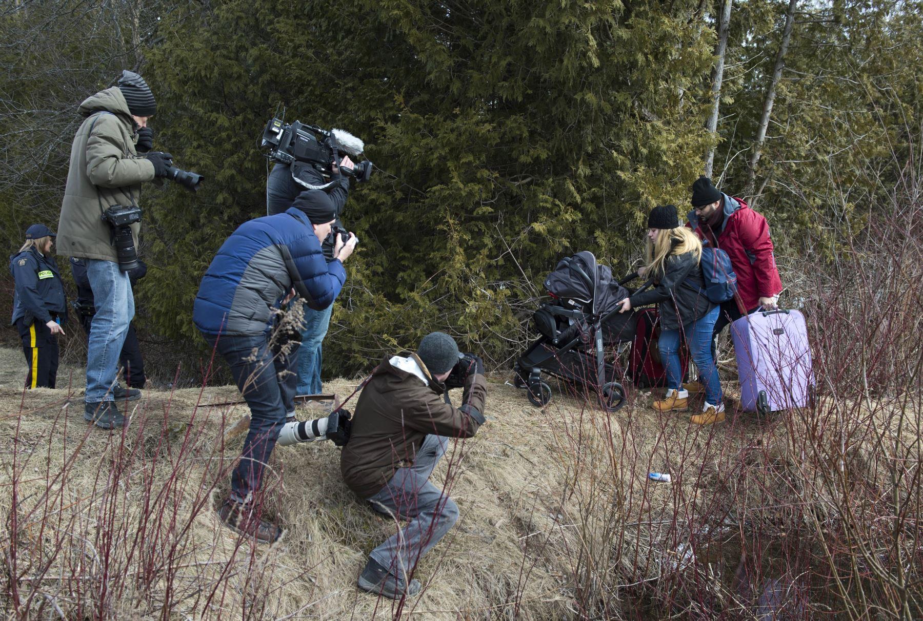 Miembros de la prensa fotografían a una pareja que decía ser de Turquía después de cruzar la frontera entre Estados Unidos y Canadá. Foto: AFP