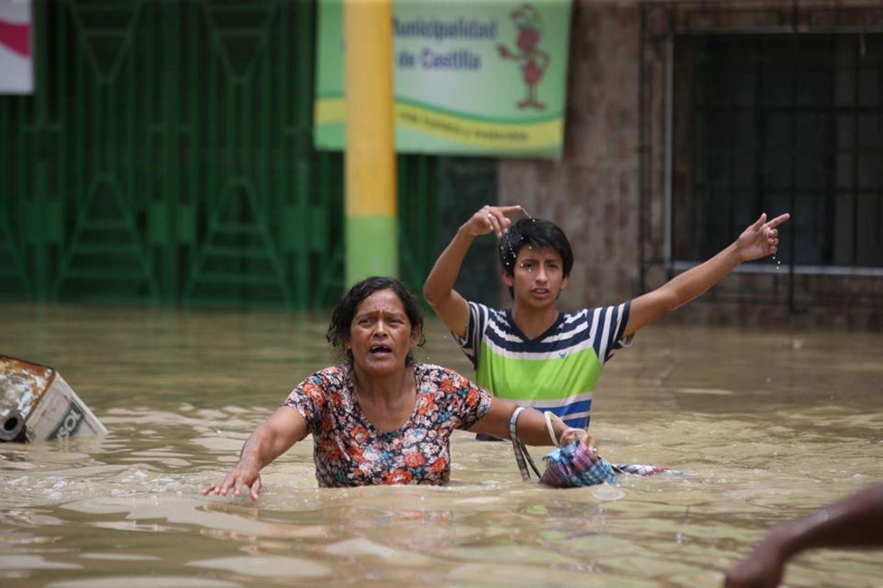 Pobladores afectados por desborde del río Piura en el distrito de Castilla, se trasladan por las calles inundadas.