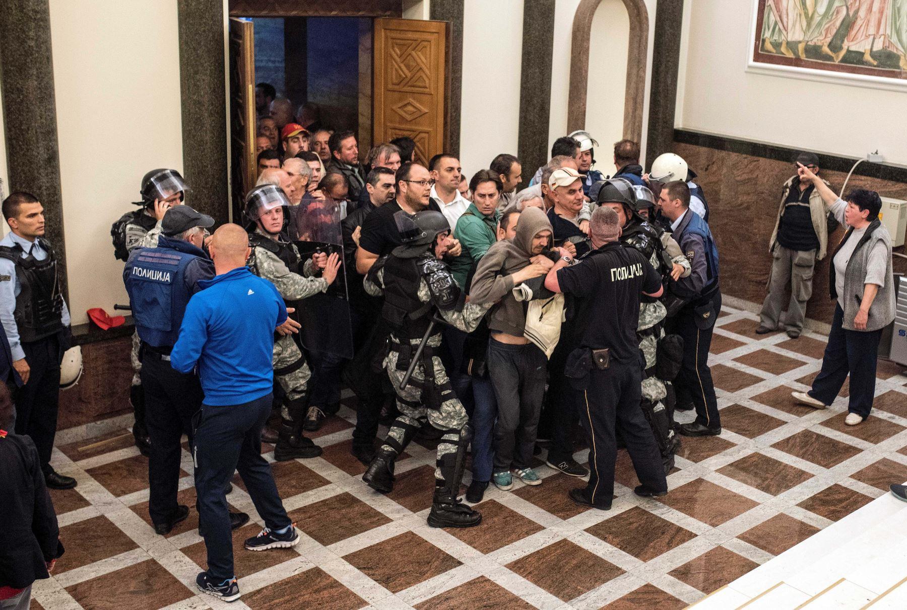 Policías tratan de contener a los manifestantes que intentan ingresar al parlamento de Macedonia. Foto: AFP