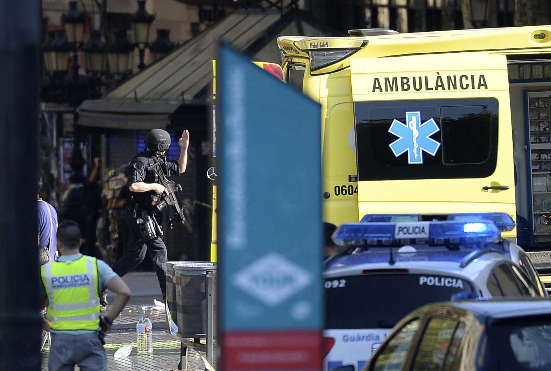 Un policía armado llega a un área acordonada después que una furgoneta atropelló a varias personas en la Rambla de Barcelona. Foto: AFP