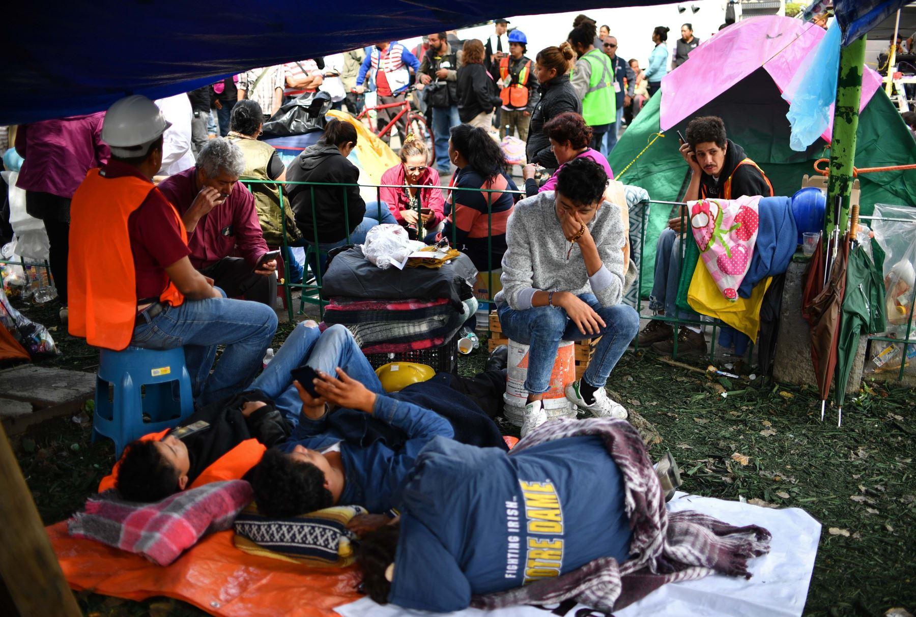 Los familiares de desaparecidos toman un descanso mientras esperan noticias ante un edificio derrumbado en la ciudad de México.Foto:AFP