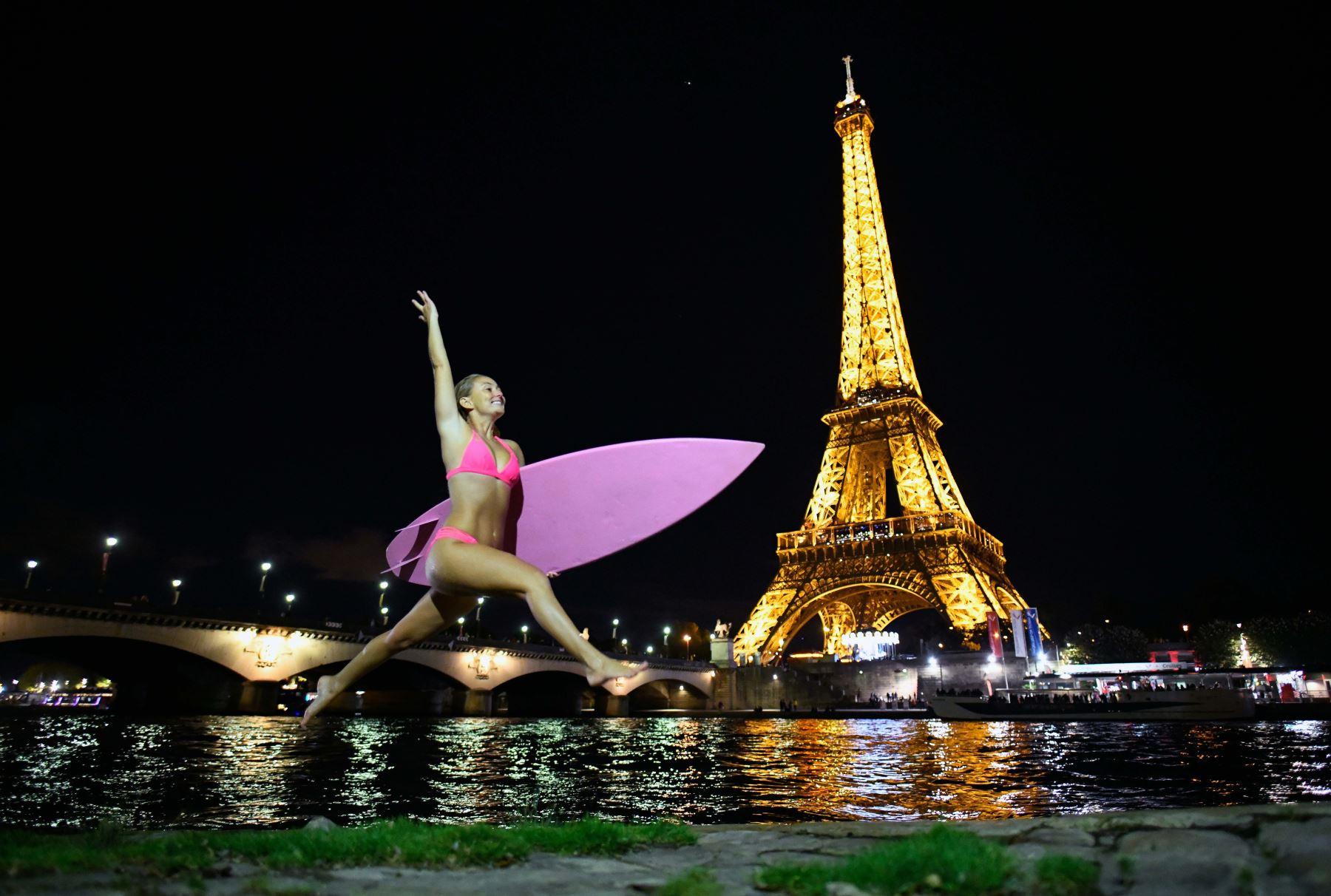 La surfista y aventurera estadounidense Alison Teal salta con sus olas junto al río Sena frente a la Torre Eiffel en París, para respaldar los esfuerzos para combatir el cambio climático.Foto:AFP