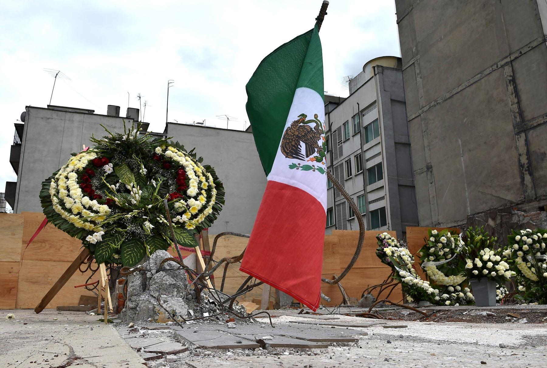 Coronas y BANDERA AMEXICANA fueron colocados para honrar a los muertos en el sitio donde un edificio fue aplastado por un fuerte terremoto en México. Foto:AFP