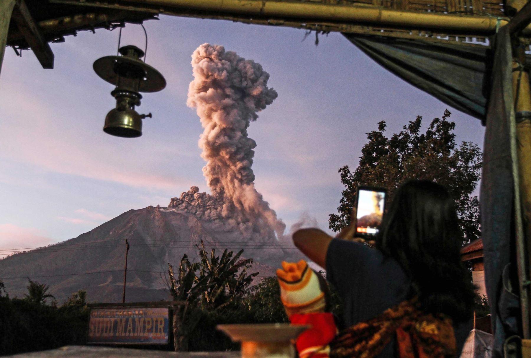 Un aldeano indonesio toma una foto del volcán Monte Sinabung mientras arroja un denso humo en Sumatra del Norte. Foto: AFP