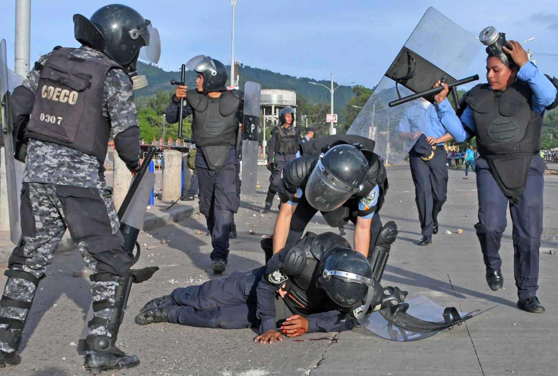 Un agente de seguridad es ayudado por sus colegas luego de ser herido durante los enfrentamientos con estudiantes en Honduras. Foto: AFP