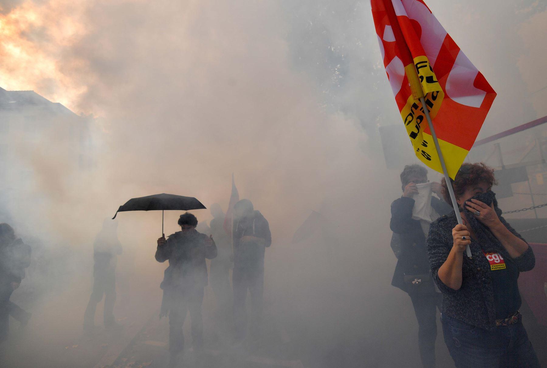 Manifestantes se cubren la cara mientras participan en una manifestación en Francia. Foto: AFP